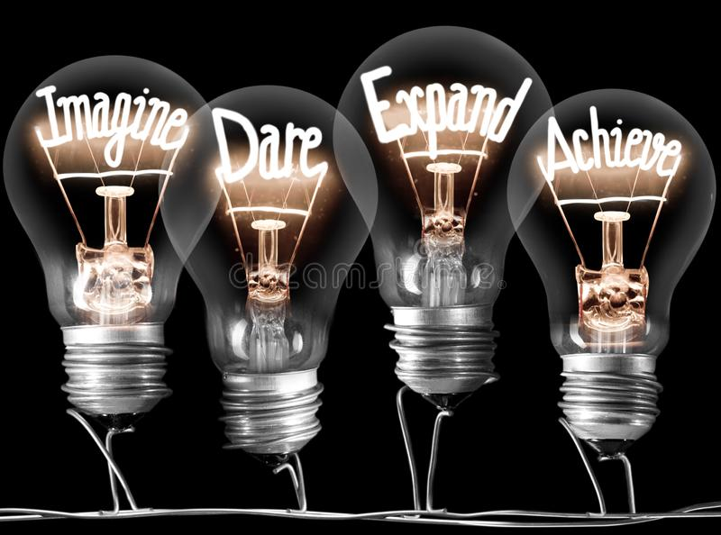 Imagine, Dare, Expand and Achieve Concept. Photo of light bulbs with shining fibres in IMAGINE, DARE, EXPAND and ACHIEVE shape on black background; concept of royalty free stock photos