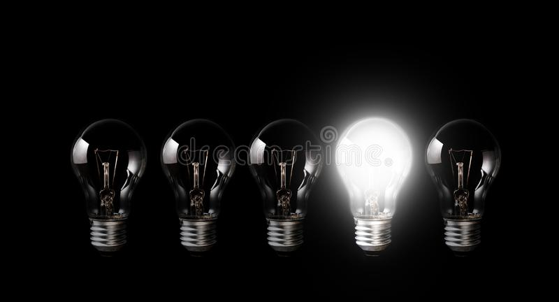Light bulbs with glowing one outstanding dark background.Business, motivation concept ideas. stock images