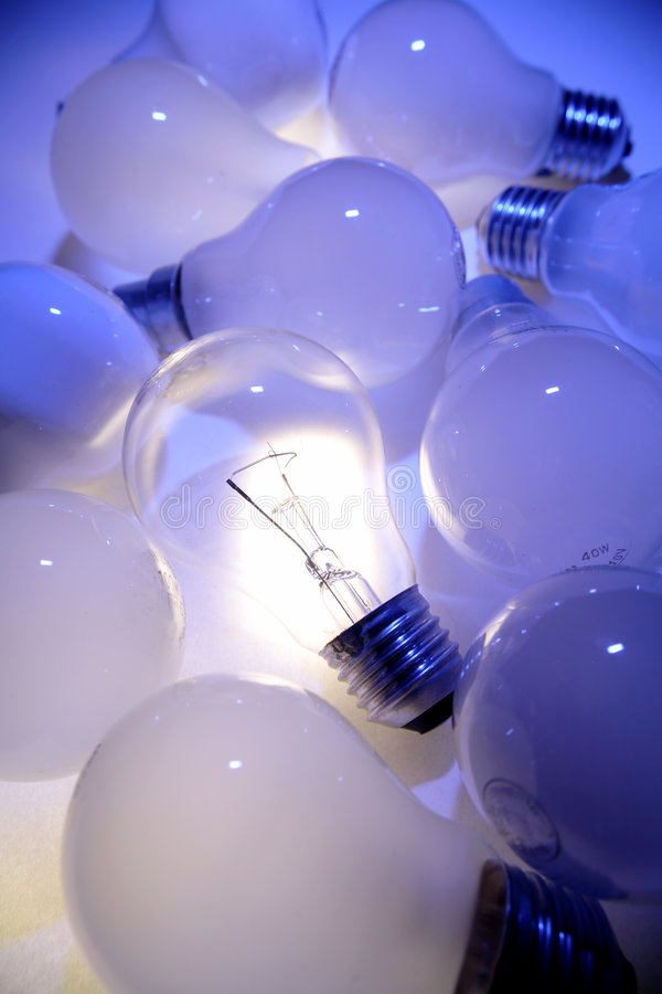 Light bulbs in a pile. A pile of light bulbs with one light bulb lit up stock image