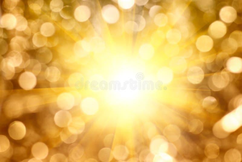 Light burst on golden sparkling. Light burst through blurry golden sparkling background
