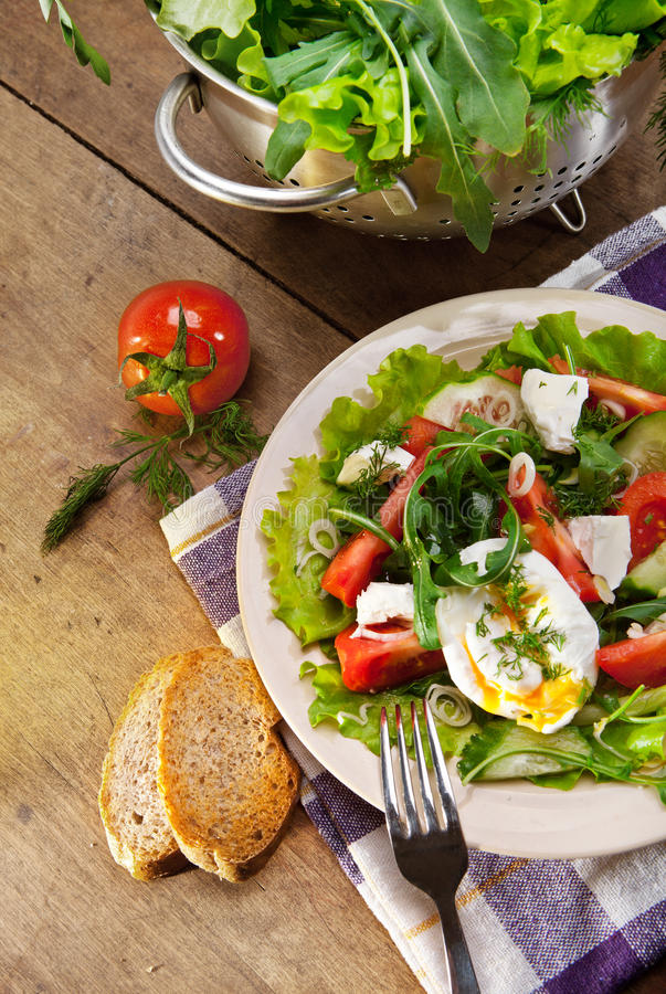 Fresh lidht salad with poached egg. Light caloried salad with fresh rucola, tomatoes and poached egg royalty free stock photo