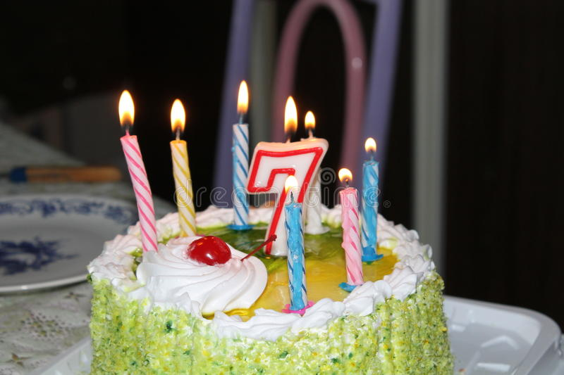 A light candle in darkness of birthday chocolate cake.  stock photography