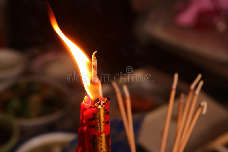 The light of candle and incense on the table food for spirits in Chinese Ghost Festival. Focus at the candle and incense stock image