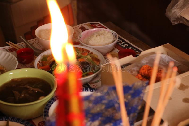 The light of candle and incense on the table food for spirits in Chinese Ghost Festival. Focus at the oblation stock photography