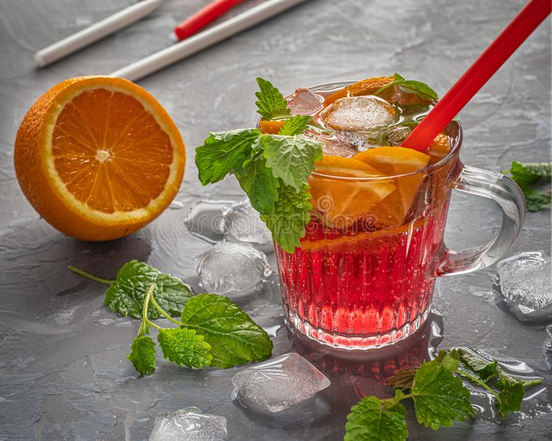 A light carbonated cherry drink with orange slices and pieces of ice, mint leaves and a cocktail tube to quench thirst on a hot. Day, pieces of ice and royalty free stock images