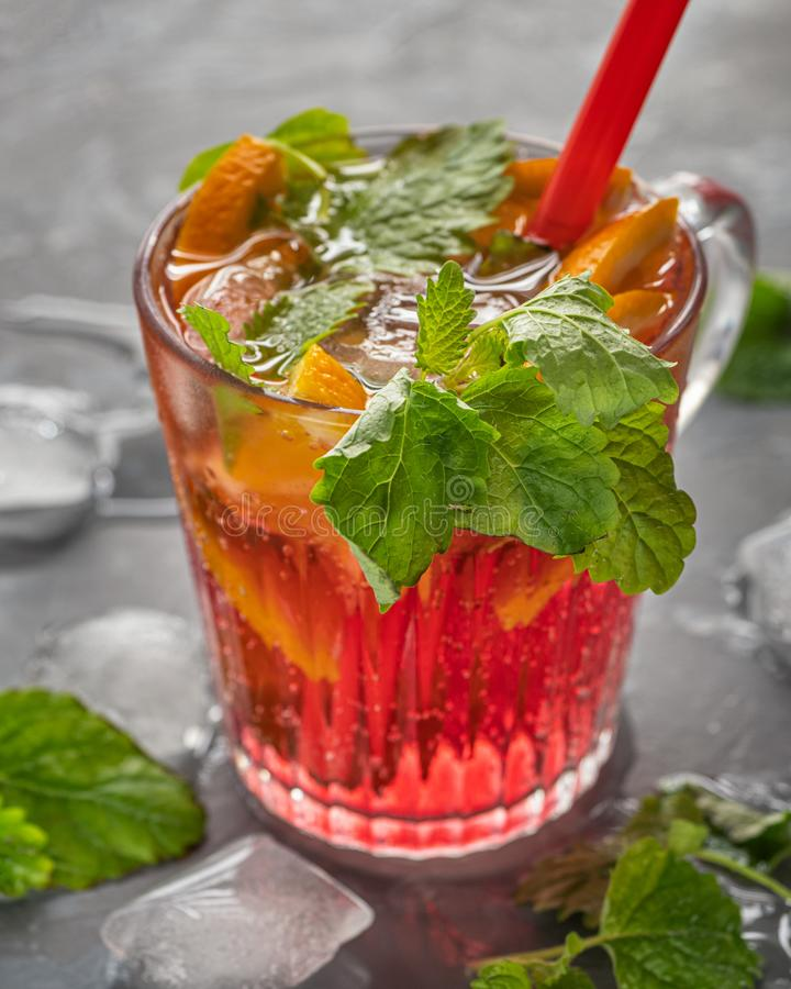 A light carbonated cherry drink with orange slices and pieces of ice, mint leaves and a cocktail tube to quench thirst on a hot. Day, pieces of ice are stock photos