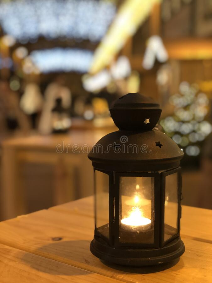 Christmas lamp with candle. The light in Christmas lamp that is standing on the wood table, night colors are shining with calmness and tenderness stock photo