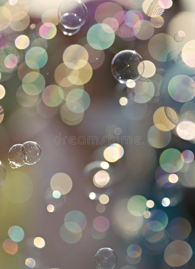 Light colored soap bubbles Bokeh Background. Flying water, soap bubbles with watercolor background. Blue, green, yellow, pink light bokeh blur background. Summer