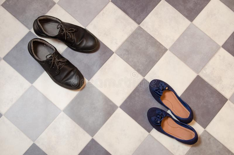 Light and comfortable blue women`s shoes and man`s shoes on  black and white checkered floor royalty free stock photos