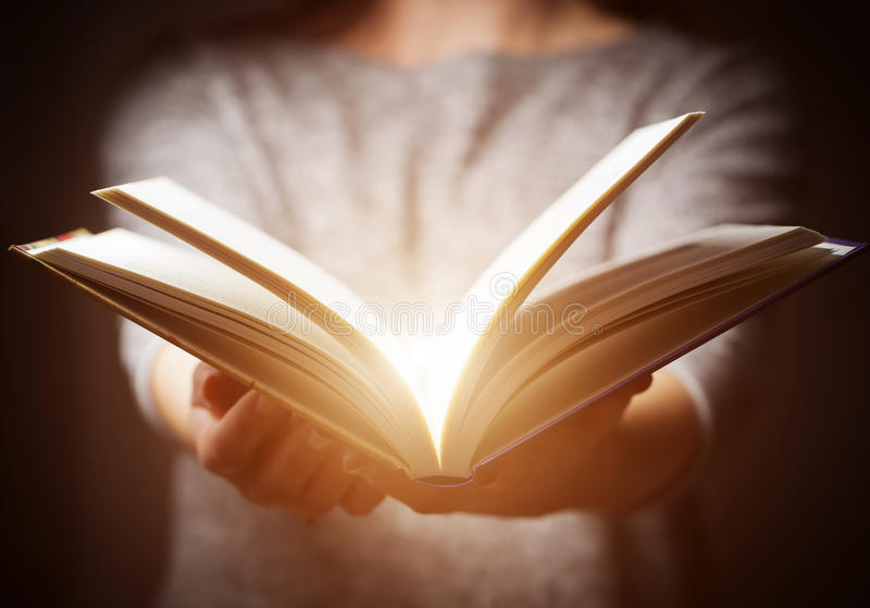Light coming from book in woman's hands in gesture of giving. Offering. Concept of wisdom, religion, reading, imagination stock photos