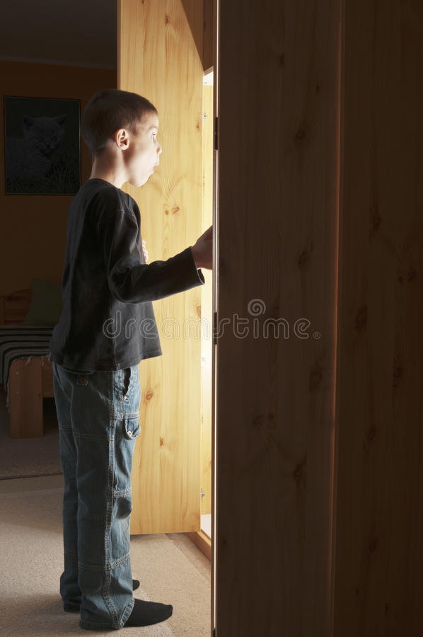 Light coming out from cupboard. Boy opening a cupboard and bright lit illuminate him stock photo