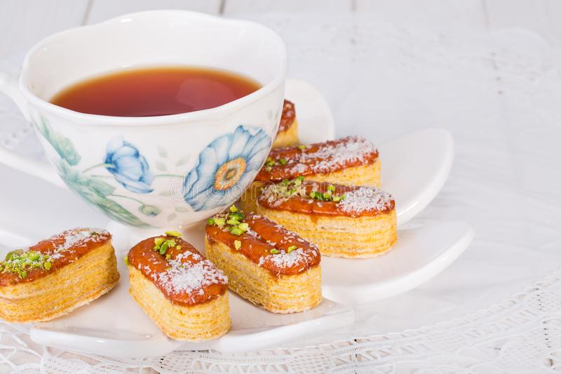 Light Crunchy Puff Layered Pastry Garnished With Pistachios & Co. Conut Flakes And Cup Of Tea Popular Persian Sweets In Iran Called Zaboon Or Zaban stock images