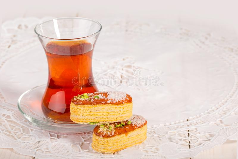 Light Crunchy Puff Layered Pastry Garnished With Pistachios & Co. Conut Flakes And A Traditional Cup Of Tea Popular Persian Sweets In Iran Called Zaboon Or Zaban royalty free stock images