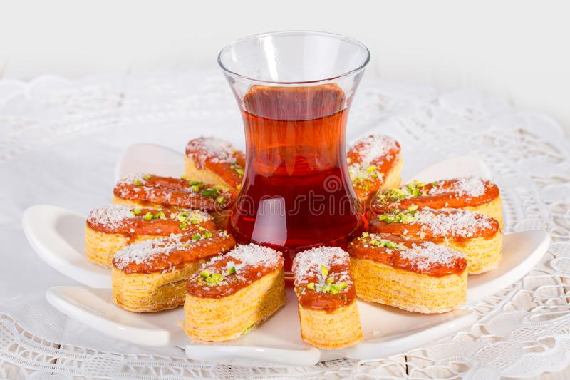 Light Crunchy Puff Layered Pastry Garnished With Pistachios & Co. Conut Flakes And Cup Of Tea Popular Persian Sweets In Iran Called Zaboon Or Zaban royalty free stock image