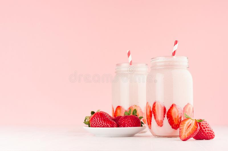 Light dairy strawberry drinks in trendy jars with ripe pieces berries on saucer, red striped straws on gentle pink background. stock photography