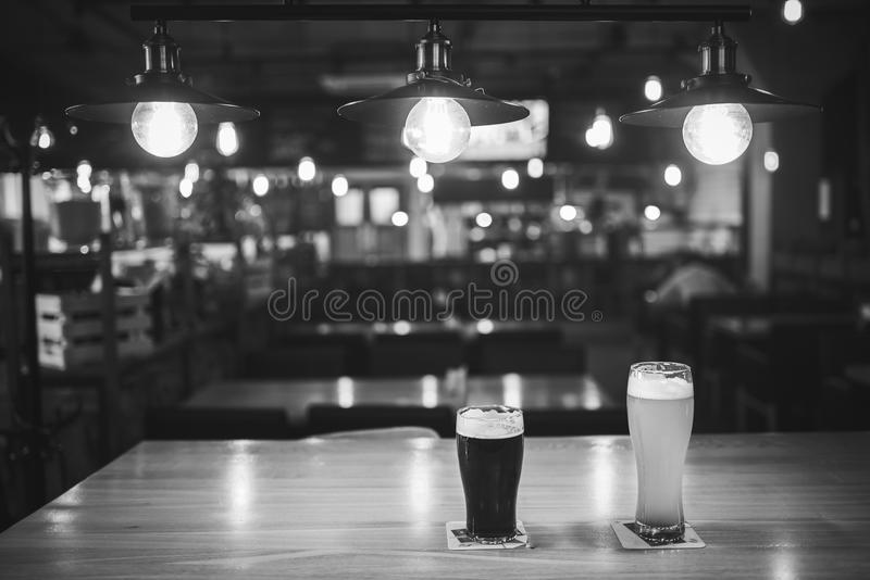 Light and dark beer in glasses on a table in a bar under vintage lamps, black and white frame. stock images