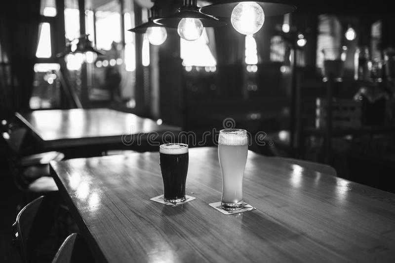 Light and dark beer in glasses on a wooden table in a bar, black and white frame stock photos