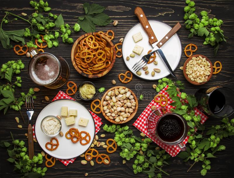Light and dark beer in mugs and salty snacks and nuts, dark wooden table, frame with copy space, top view. Light and dark beer in mugs and salty snacks and nuts stock photo