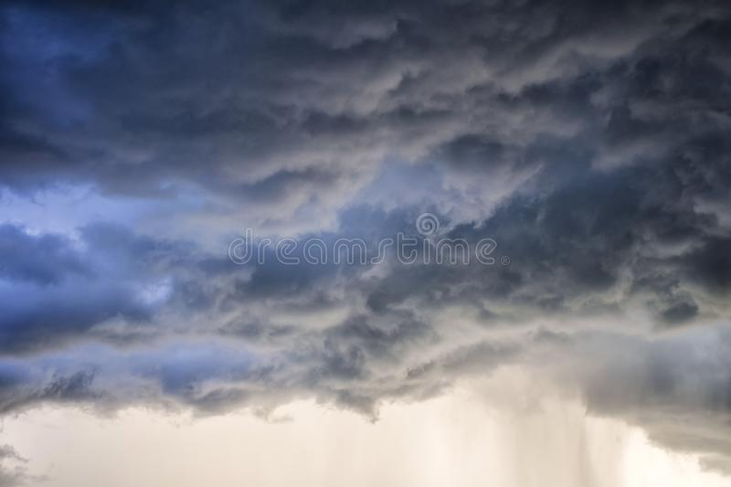 Light in the Dark and Dramatic Storm Clouds background. Black cumulus clouds before the beginning of a strong storm atmosphere backdrop beautiful blue bright stock image