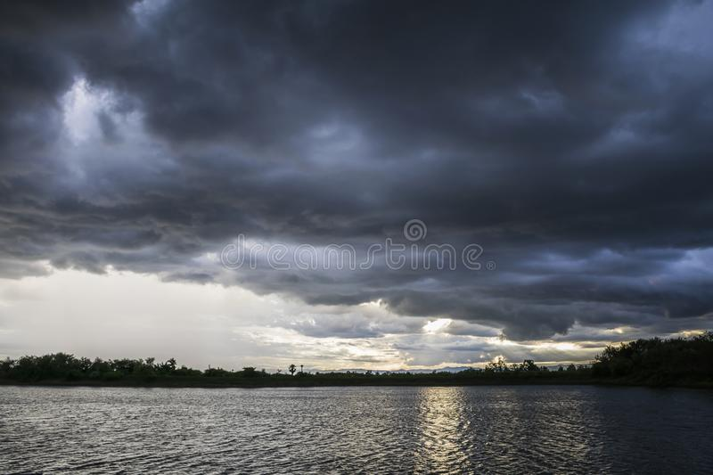 Light in the Dark and Dramatic Storm Clouds background. Black cumulus clouds before the beginning of a strong storm atmosphere backdrop beautiful blue bright royalty free stock photo