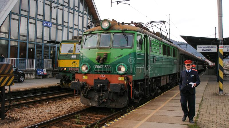 Polish electric locomotive EU07 with international train in Cadca in Slovakia. Light and dark green livery of universal electric loco serving international stock photography