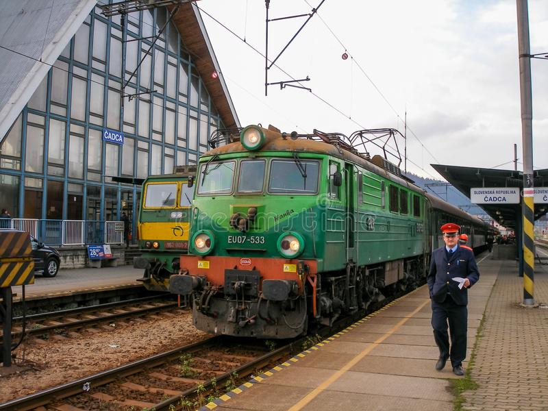 Polish electric locomotive EU07 with international train in Cadca in Slovakia. Light and dark green livery of universal electric loco serving international royalty free stock photography