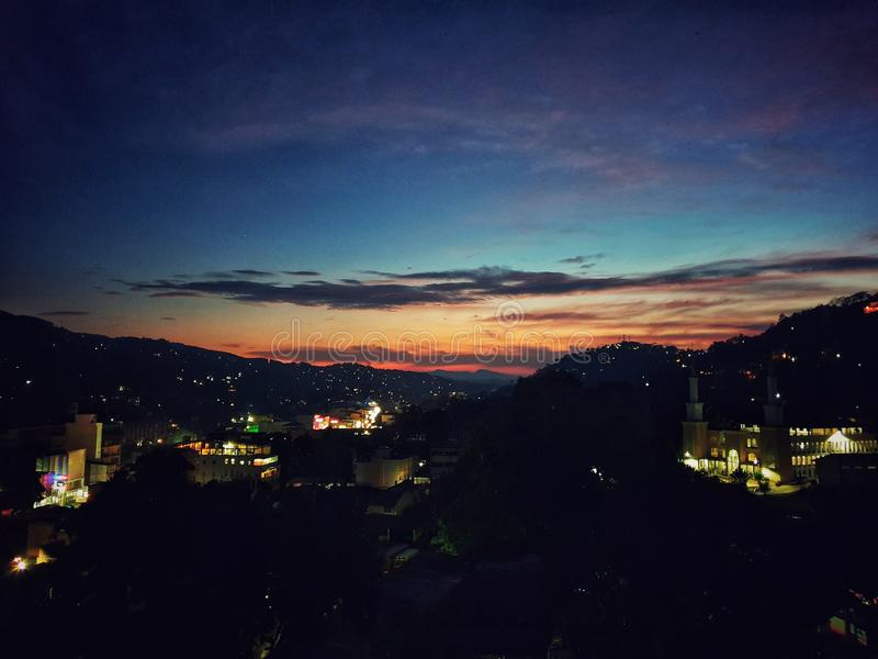 Light doesn& x27;t fade even when the sun goes down. Doesnt, mountains, blue, orange, sunset, sky, town, valley stock photography