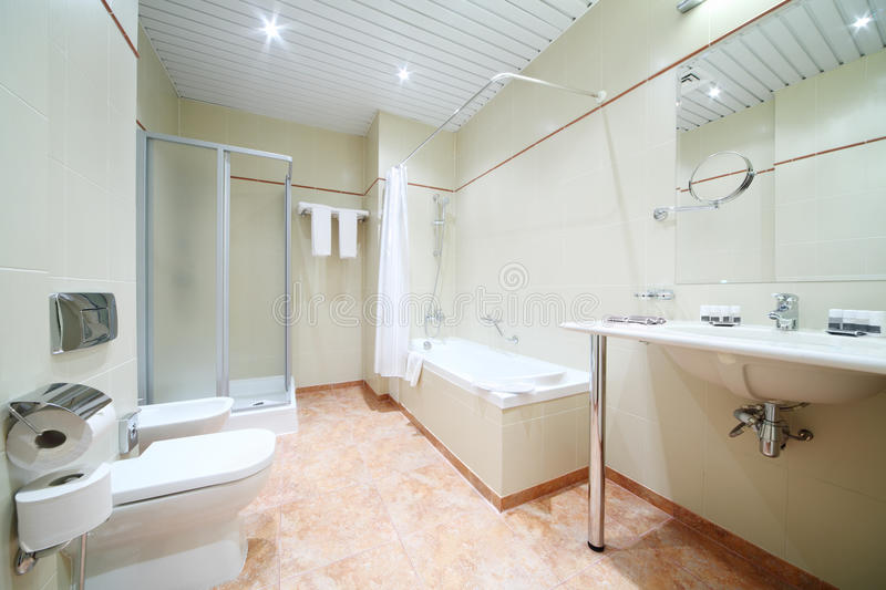 Light and empty bathroom with white bath, toilet. And shower cabin stock image