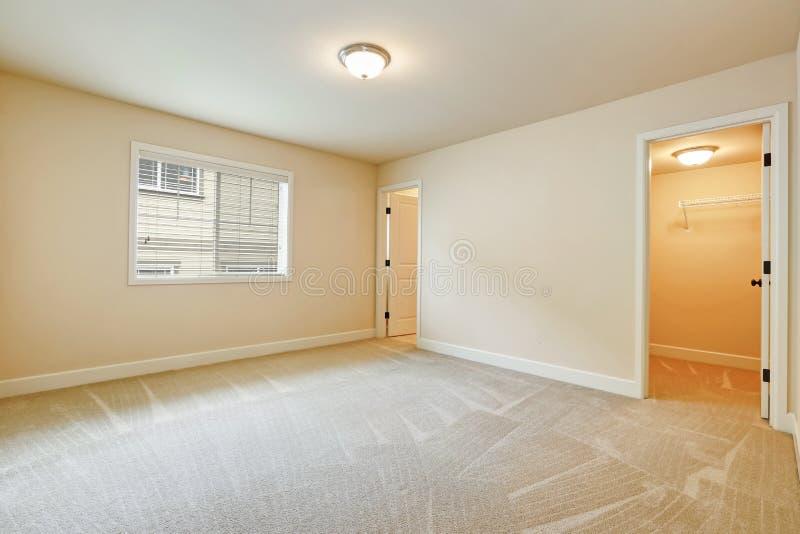 Light empty bedroom interior in beige tones. Light empty bedroom interior with soft sand beige walls paint color, walk in closet and own bathroom. Northwest, USA stock photos