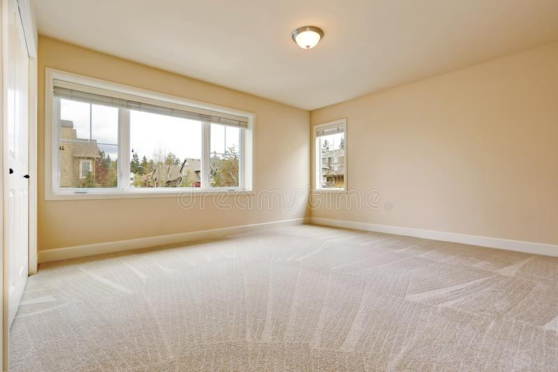 Light empty bedroom interior in soft beige tones. Light empty bedroom interior with soft sand beige walls paint color, walk in closet and wall to wall carpet royalty free stock photography