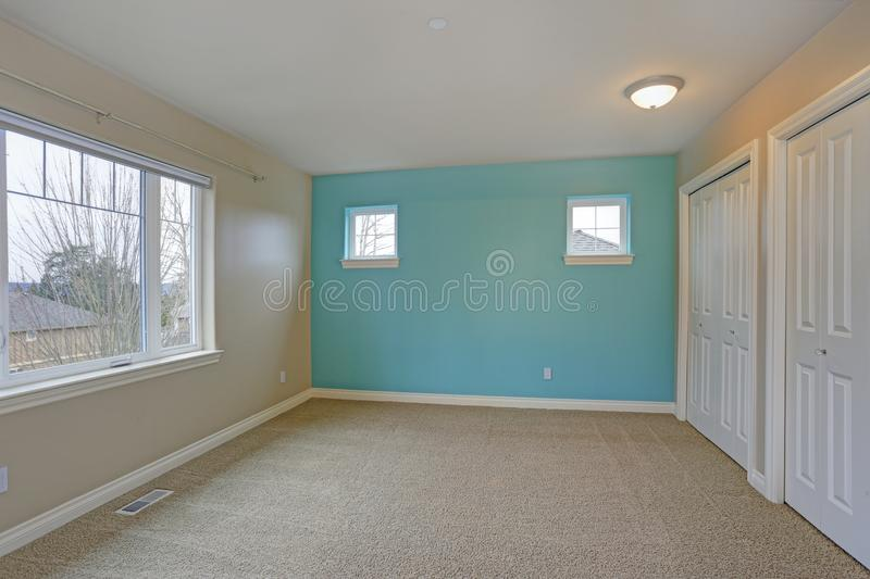 Light empty room interior with focus on a bright blue wall. Light empty room interior with accent blue wall, built in closet, carpet floor royalty free stock photography
