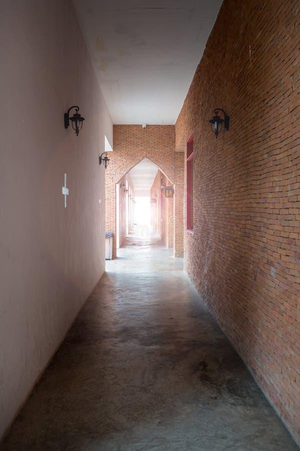 Light at the end of corridor. Ancient walk way made from red brick wall. Light at the end of corridor. Ancient walk way made from red brick outside hall royalty free stock photo