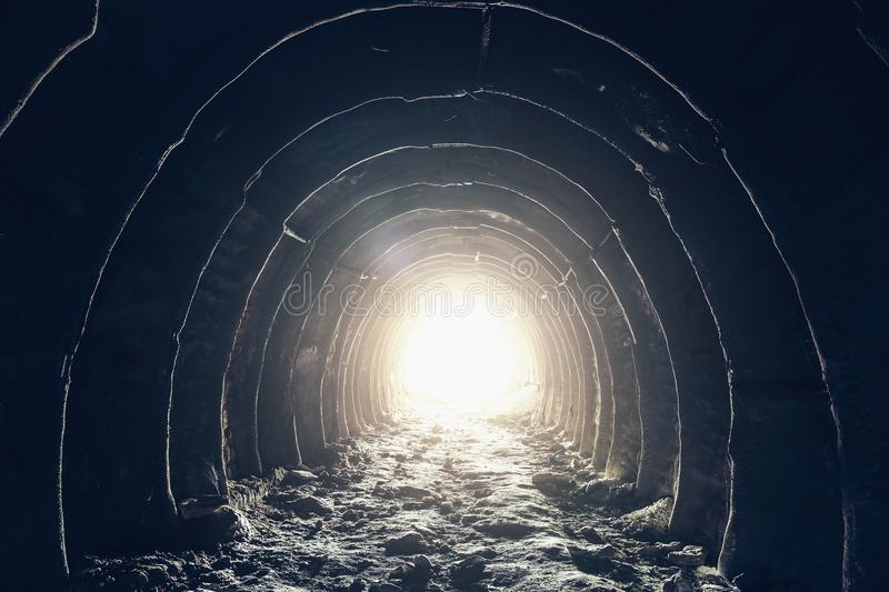 Light at the end of dark industrial tunnel, abandoned underground cave or mine, exit or escape to freedom light concept stock photo