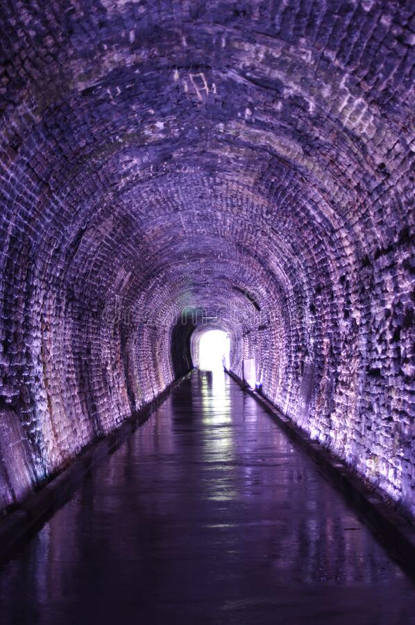 Light at the end of old brick railway tunnel stock images