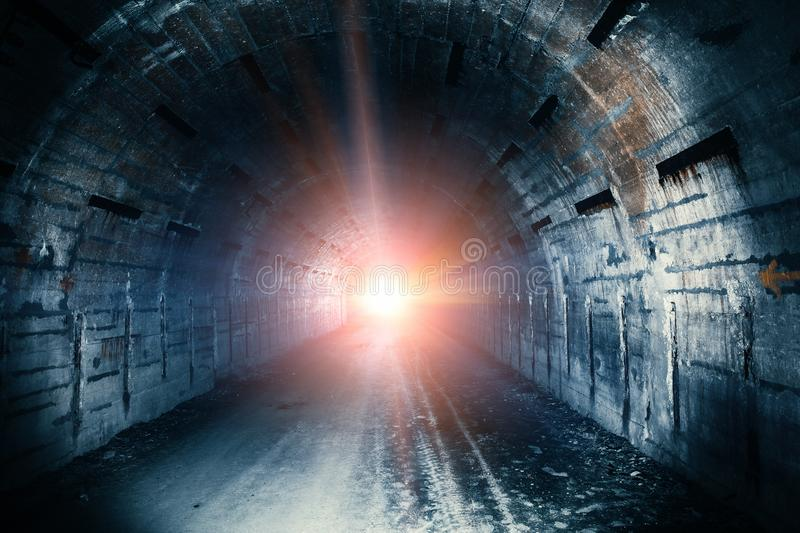 Light in end of tunnel. Long underground concrete corridor in abandoned bunker stock image