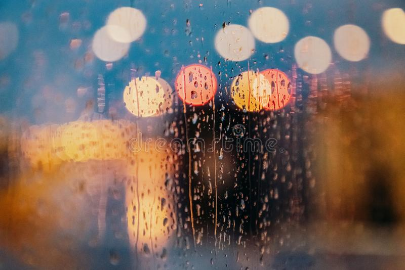 Light of evening city and rain drops on the window. Abstract blurred background. Bright light of evening city and rain drops on the window. Abstract blurred stock images