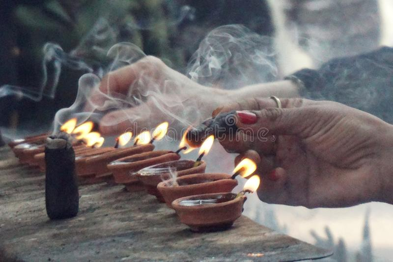 Insence and burning light and femenine hand. Light is everywhere the symbol of joy and of life-giving power, as darkness is of death and destruction. Fire is an stock photo