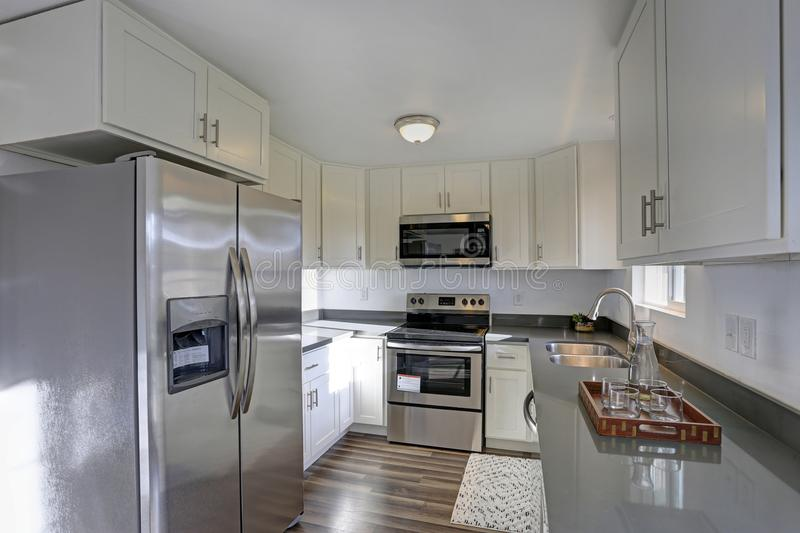 Light filled home interior features small compact kitchen. With white cabinets and modern stainless steel appliances stock photography