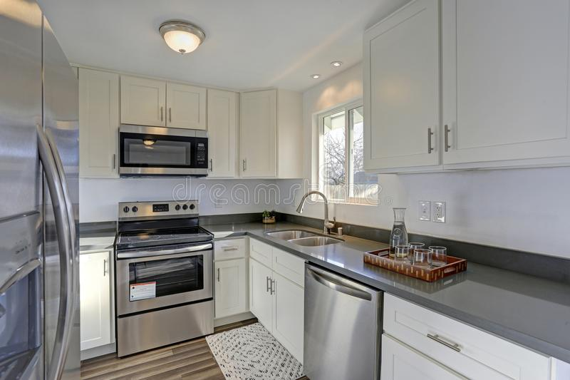 Light filled home interior features small compact kitchen. With white cabinets and modern stainless steel appliances royalty free stock photo