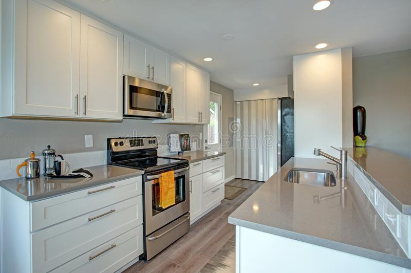 Light filled kitchen with stainless appliances. White cabinets topped with quartz counters and hardwood floor royalty free stock photo