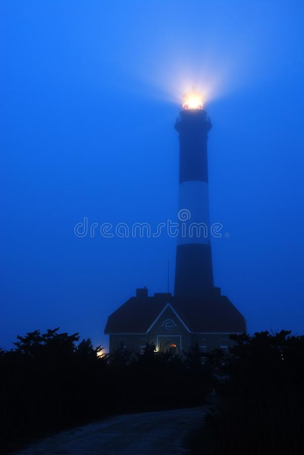 Foggy Beacon. The light from the Fire Island Lighthouse projects through a foggy night royalty free stock image