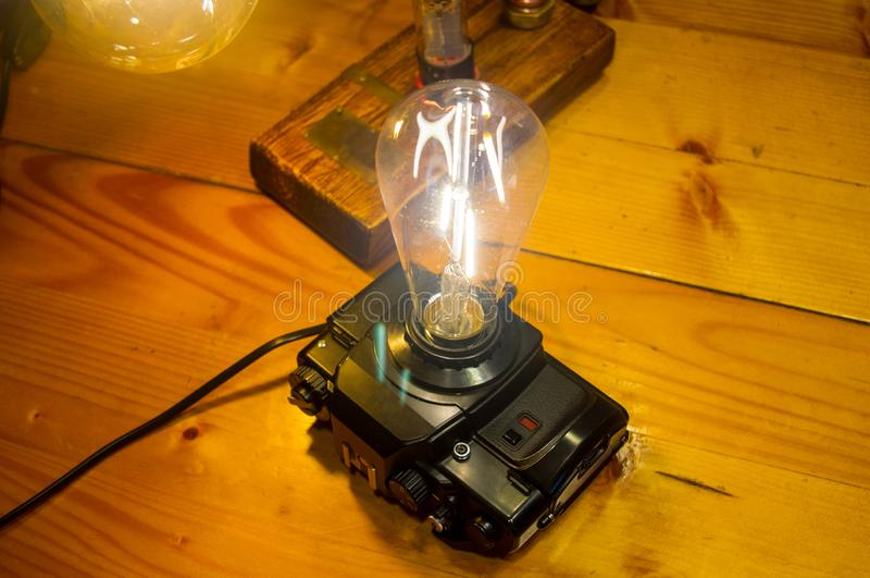 Light fixture handmade in vintage style, retro film SLR camera case. Led lamp stock photos