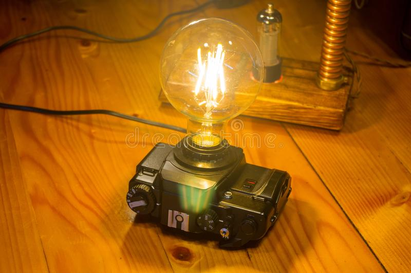 Light fixtures handmade in vintage style, retro film SLR camera case and wooden case. Led lamps royalty free stock images