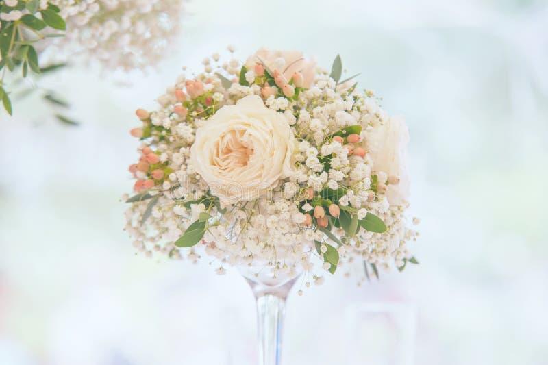 Light floral wedding decoration in elegant glass vase central composition stock images