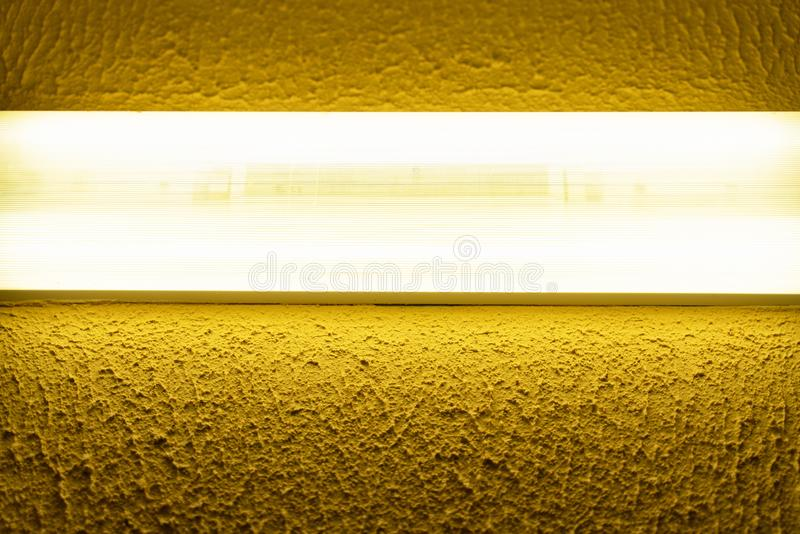 Light fluorescent lamp with white light on the wall with yellow embossed surface. Light fluorescent lamp with white light on the wall with yellow surface royalty free stock photos