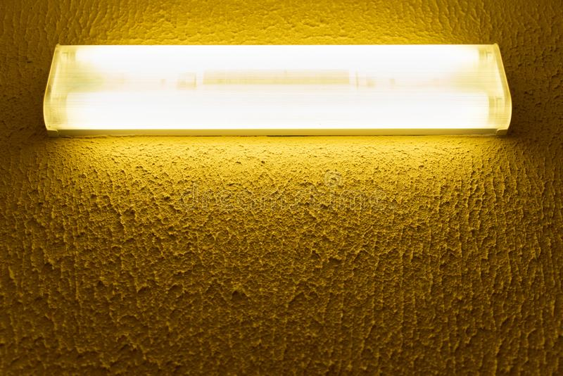 Light fluorescent lamp with white light on the wall with yellow embossed surface. Light fluorescent lamp with white light on the wall with yellow surface royalty free stock images