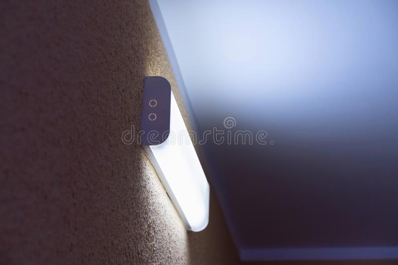 Light fluorescent lamp with white light on the wall with yellow embossed surface. Light fluorescent lamp with white light on the wall with yellow surface stock images