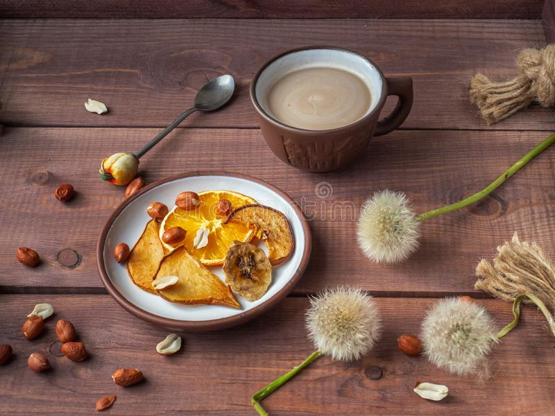 Light fruit chips and peanut nuts for light morning coffee with milk on a wooden rustic tray royalty free stock image