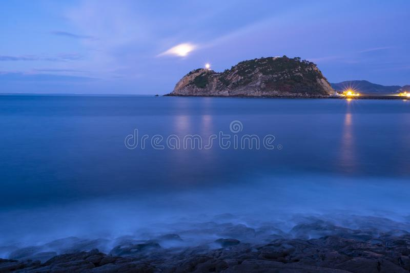 Light of Getaria lighthouse and fullmoon over the sea at night. Light of Getaria lighthouse and fullmoon over the sea at night, Euskadi stock photo