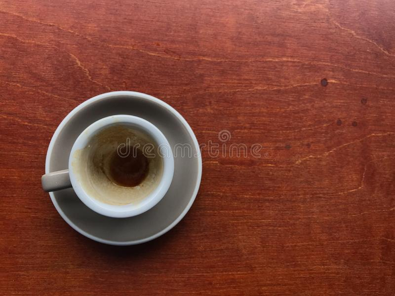 Light gray cup and saucer of finished espresso coffee with stained brown coffee in a cup on brown wooden table stock photos